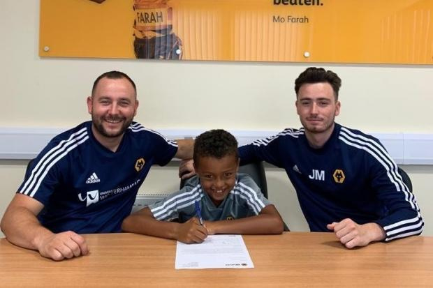 SIGNED: Kobe Otun signing his contract with Tom and Jack Maydew from Wolves